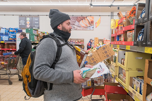 Joe Muehlbauer decides which food products to buy at Aldi's as he participated in Key City Bike's second annual Cranksgiving alley cat, a bike race that benefited the Committee Against Domestic Abuse. Photo by Jackson Forderer