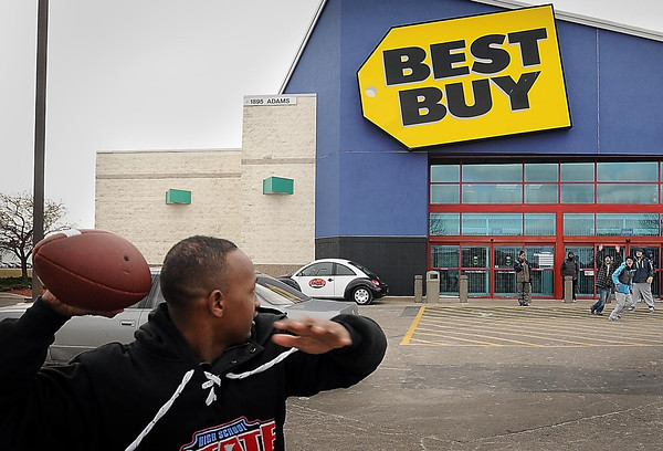 John Cross<br /> Abdi Fatah engages in a game of parking lot football with other early shoppers who also had claimed a place in line early on Thanksgiving Day for the 6 p.m. opening of Best Buy.