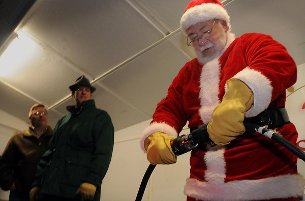 John Cross<br /> Mankato Mayor Eric Anderson (left) and North Mankato Mayor Mark Dehen watch Santa Claus plug in extension cords to light the Kiwanis Holiday L:ights display Friday in Sibley Park.