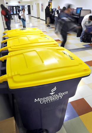 Students walk past new purple and gold recycling containers in Minnesota State University's Wigley Administration Center Wednesday. The university started a new contract Wednesday with North Mankato's LJP Waste and Recycle that will save the univeristy $25,000 annually while increasing its level of recycling. The new branded bins in campus buildings and new purple colored outside compactors and containers are part of the new contract.