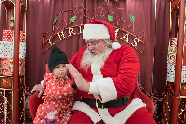 Briana Benson, 3, from Albert Lea gives Santa Claus a high five after giving him an extensive list of what she wanted for Christmas at the opening night of Kiwanis Holiday Lights on Friday at Sibley Park. Photo by Jackson Forderer
