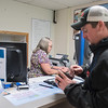 Blake O'Rourke (right) puts his debit card back in his wallet as Rose Cline helped him renew his license on Wednesday at the Blue Earth County License Center. Photo by Jackson Forderer