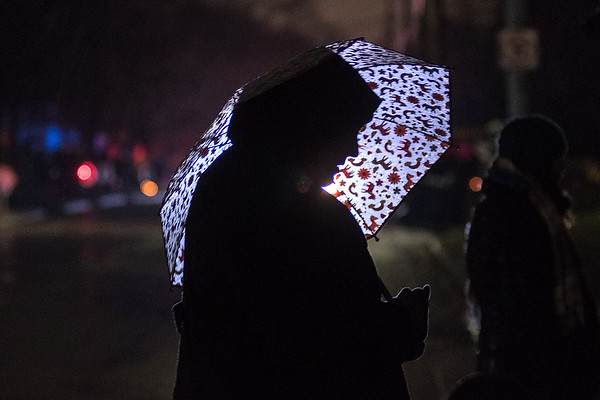 Jaci Baker waits for the start of the Kiwanis Holiday Lights Parade along Mound Avenue under her umbrella. Crowds faced a wet start to this year's holiday lights event. Photo by Jackson Forderer
