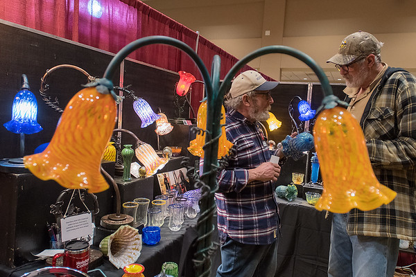 Steven Weagal of Weagalworks shows Tom Hall (right) a piece of blown glass in his booth at the GSR Fine Art Festival held on Saturday. Weasel said he uses steel instead of copper for the posts in his lamps. Photo by Jackson Forderer