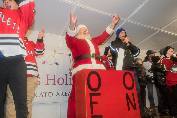 Santa Claus throws his arms up after turning on the lights to the crowd's delight at Kiwanis Holiday Lights in Sibley Park on Friday. Photo by Jackson Forderer