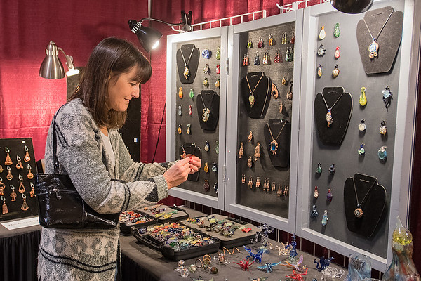 Lisa von Holt looks at items for sale in the Mankato Makerspace booth at the GSR Fine Art Festival held on Saturday at the Verizon Center. Photo by Jackson Forderer