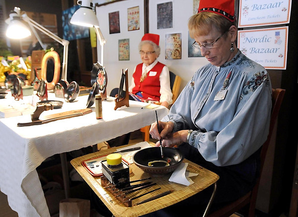 Mary Sherwood rosemals a bowl as Teddy Ollrich tends to a table of her wares at Bethlehem Lutheran Church's Nordic Bazaar Wednesday.