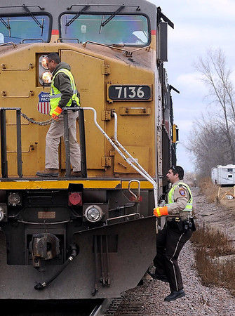 Blue Earth County Sheriff's deputy Chad Ruch boards a Union Pacific locomotive.