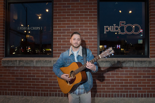"Anthony Flynn outside of Pub 500, where he has played at open mic night many times. Flynn's band The Tony Flynn Project will be playing at Buster's on Nov. 18 at 11 p.m. ""Let's keep that going, that tradition is awesome,"" Flynn said about open mic nights. Photo by Jackson Forderer"