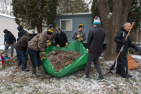 Members of the Mankato East boys hockey team pick up a tarp filled with leaves as they cleared a yard in Eastwood Manor as part of Rake the Town on Saturday. Photo by Jackson Forderer