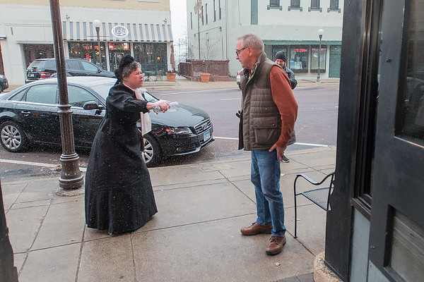 Ellie Carlson, portraying famous prohibitionist Carry Nation, pours out Mark Windschitl's drink outside of the B+L Bar in New Ulm on Thursday. Photo by Jackson Forderer
