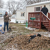 Tyler Schlaak takes a brief break from making leaves and makes an angel in a pile of leave while Connor Welle takes his picture at Eastwood Manor on Saturday. At right, Eric Van Otterloo talk to homeowner Marilyn Hagge as volunteers from VINE cleared her yard of leaves. Photo by Jackson Forderer