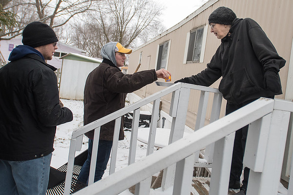 Roselyn Ellingson (right), gives out snacks to Ahn Enright (center) and Chris Frey (left) as they arrived to rake her yard on Saturday morning during the Rake the Town event. The event is organized by VINE to help homeowners clear leaves off of their lawn. Photo by Jackson Forderer