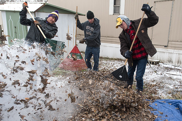 Ahn Enright (right), Triston Sackett (center) and Tanner Oleson rake leaves onto a tarp in Roselyn Ellingson's yard at Eastwood Manor on Saturday during the Rake the Town event organized by VINE. Photo by Jackson Forderer