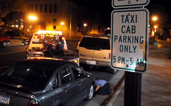 A tow truck driver from All American Towing moves a car parked in the new taxi cab parking zone Saturday night.