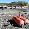 John Cross<br /> A barrier bouy is high and dry on mud flats on the upstream side of the Rapidan Dam on the Blue Earth River. Generators at the facility have been shut down because the river flow has fallen to 19 cubic feet per second, rivialing the record low flow of 18 cubic feet per second that dates back to 1958.