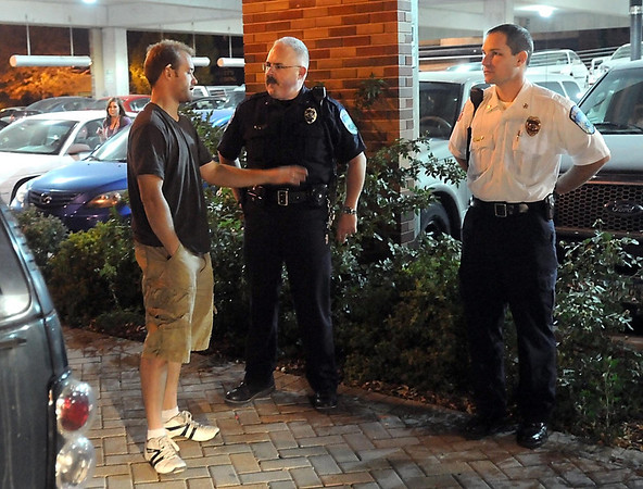 Mankato Department of Public Safety deputy director Matt Westermayer (center) talks with a person near the new taxi cab loading zone on South Second Street Saturday night.