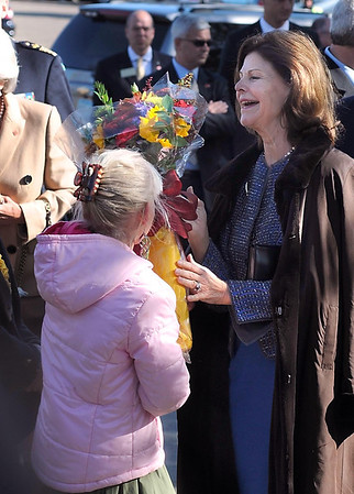 Queen Silvia of Sweden accepts a bouquet of flowers from St. Peter third grader Anja Koij, who greeted the queen in Swedish, Friday at Gustavus Adolphus College.