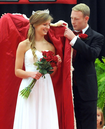 Pat Christman <br /> Mankato West homecoming queen Maria Soroka has a robe placed on her by her escort Kier Oxnard during the school's coronation ceremony Friday.