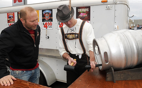 Pat Christman <br /> Mankato Brewery's Tim Tupy, left, and North Mankato mayor Mark Dehen tap a special keg of the brewery's Leaf Raker beer during Bier on Belgrade Saturday.