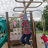 Ruby Byers, 7, climbs across the monkey bars at Southview Park on Saturday. The City of Mankato is planning to put in two new playgrounds, similar to the one at Southview, in two new parks. Photo by Jackson Forderer
