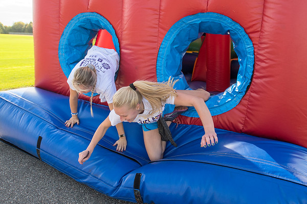 Taryn Banheel (left) and Leah Schiefert nearly fall as they climb out of one the inflatable obstacles at the Inflatable 5K  put on by the Student Events Team at Minnesota State University. Photo by Jackson Forderer