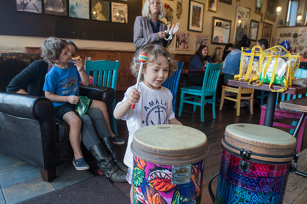 Zain Haque (center), 3, plays on a pair of drums at the Coffee Hag on Wednesday where organizers gathered to sing protest songs as visa delays caused London-based Aar Maanta to cancel his trip to Mankato. Photo by Jackson Forderer
