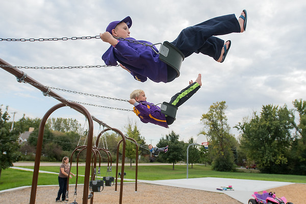 Casey Fogal (top), 11, and Cameron Fogal, 9, swing at Southview Park on Saturday. The City of Mankato is looking at the park as a model for two new city parks. Photo by Jackson Forderer