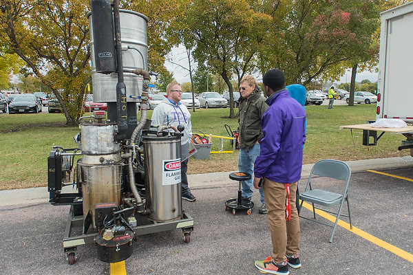 Jacob Swanson, an associate professor with the department of integrated engineering, explains his biofuel electric generator at the Recharge Mankato event on Saturday. Unlike generators that can be purchased in a store that run on gas, Swanson's generator uses wood or any other source of waste biomass as the fuel. Photo by Jackson Forderer