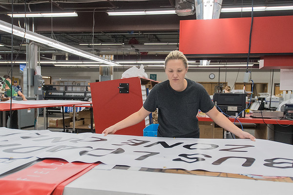 Kelly Moore, a finisher at Navitor Specialty Products unfolds a large banner at the the company's facility in North Mankato. Navitor gave tours to students and others as part of the Tour of Manufacturing on Thursday. Photo by Jackson Forderer