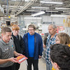 Tim Cline (lower left), an account project manager at Navitor Specialty Products, shows a sign to a class of computer science and engineering students from Mankato East as part of the larger event Tour of Manufacturing. Fifteen different manufacturers gave tours of their facilities on Thursday. Photo by Jackson Forderer