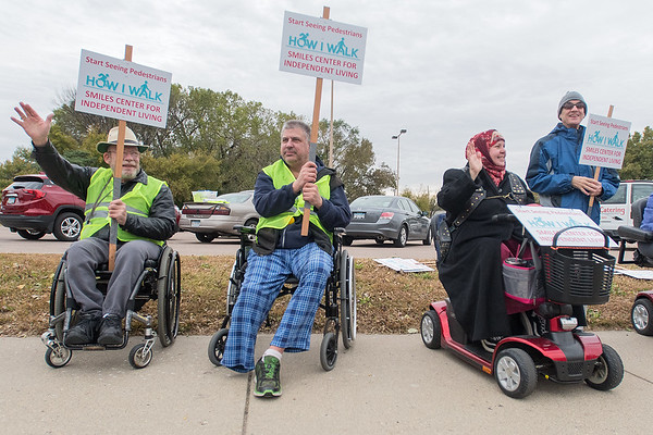 From left, Mick Emehiser, Kevin Krueger, Khadijah Fitzgerald and John Knooihuizen wave to traffic passing by along Riverfront as they promoted pedestrian awareness. Emehiser himself has been hit four times by four different cars. Photo by Jackson Forderer