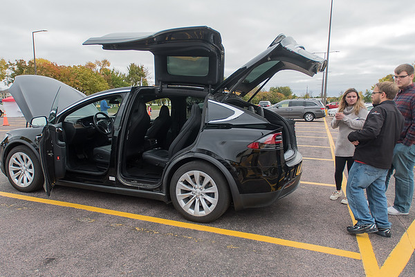 "Jay Hanke (second from right) shows a 2017 Tesla Model X to Carter Hennessy (right) and Emily Bourassa at the Recharge Mankato event put on by Minnesota State's College of Science, Engineering and Technology. ""I'm just a broke college student right now but once I finally start making money I'm sure looking forward to these,"" Hennessy of electric cars. Photo by Jackson Forderer"