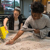 Emily Fischer (left) and Brittney Johnson, both geology majors at Gustavus, disperse sand on a stream table that they use for their geomorphology class during a demonstration as part of the Nobel Conference being held at Gustavus. Photo by Jackson Forderer