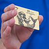 Chad Fitterer, general manager at Navitor Specialty Products, shows a sample of an engraved gift card made at the facility while he gave a tour of the business during The Tour of Manufacturing on Thursday. Photo by Jackson Forderer