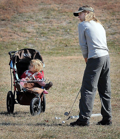 John Cross<br /> Dwight McCabe and his daughter, Monir, take advantage of Tuesday's nice weather to work on his golf stroke.