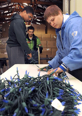 Front to back, Mankato East students Dustin Michael-Miller, Remy Peterson and Sam Rausch wind holiday lights onto a spool to help with setup of the Kiwanis Holiday Lights display Wednesday.