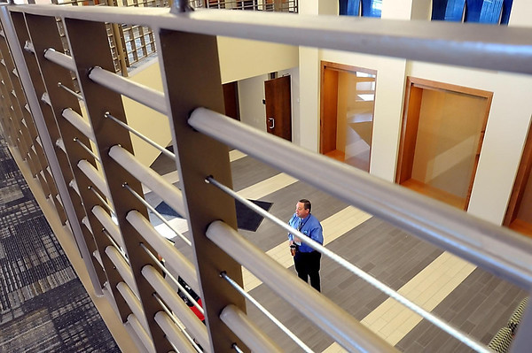 Mankato Director of Public Safety Todd Miller is framed by a railing in the entry way of the newly-remodeled Public Safety Center during a media tour Monday. The railings were constructed from old cell doors from the former Blue Earth County Jail.