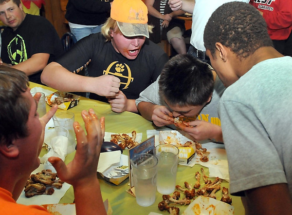 Pat Christman<br /> Mankato East football players cheer on teammate Jake Fager as he tries to finish the Buffalo Wild Wings Blazin' Challenge ahead of football players from Mankato West Thursday at the downtown Buffalo Wild Wings. Fager and his teammates finished just short of eating 60 blazin' wings ahead of the West team, but still earned a $50 donation to the program from the restaurant.