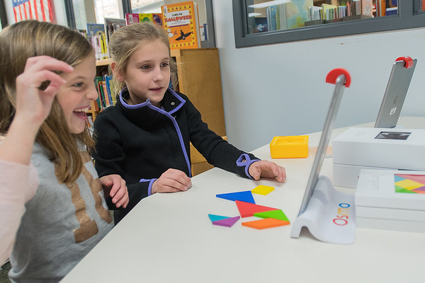 Mollie Kelly (left), 9, celebrates after she and Bryna Irvin, 9, completed arranging shapes into a horse as instructed by an iPad program called Osmo during a Makerspace class. Fourth-graders at Jefferson Elementary also used an iPad to design and play their own video game. Photo by Jackson Forderer