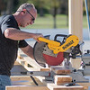 Jeff Schauer cuts a piece of wood while working on the new warming house in Spring Lake Park in North Mankato on Friday. The structure will be used asa warming house in the winter and a community room in the summer. Photo by Jackson Forderer