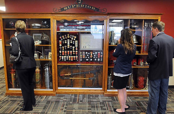 Visitors look at a case of fire memorabelia in the Mankato Fire Department's living quarters in the new Public Safety Center Tuesday.