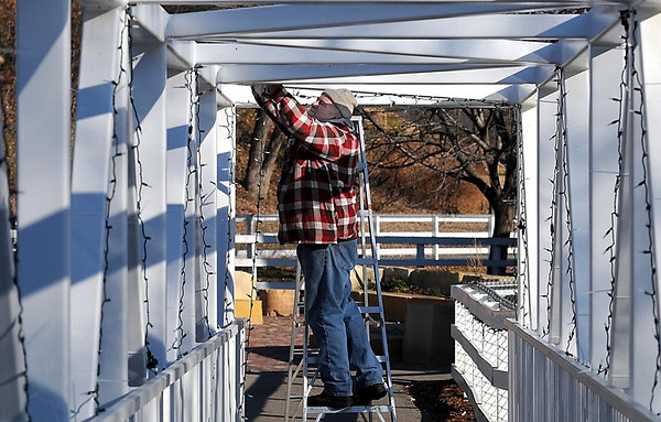 Tom Peterson puts up some of the 1 million lights that will be part of the Kiwanis Holiday Lights display Saturday in Sibley Park's farmyard.