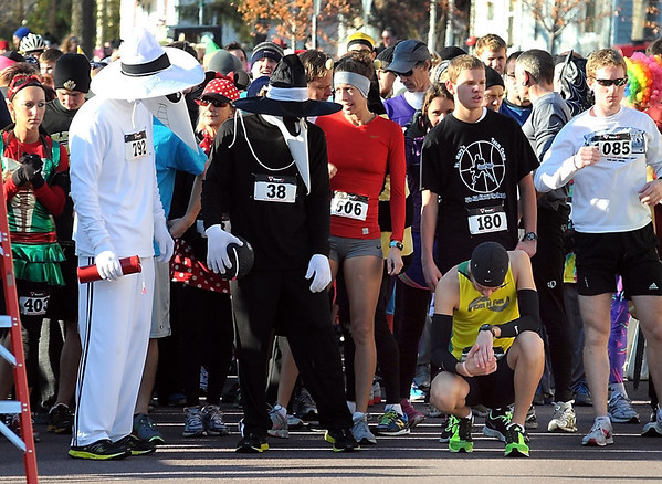 Runners dressed as Spy vs. Spy watch a more serious runner prepare for Saturday's St. Peter Halloween Fun Run start.