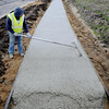 John Cross<br /> A worker finishes a freshly poured section of sidewalk adjacent to the Adams Street extension between Hope Street and North Victory Drive. The project, which replaces a temporary route that for years ran through the Madison East Center parking lot, was recently opened to traffic. Completion of the missing Adams Street link was prompted by future plans for housing and business development on a 35-acre parcel just north of the new road.