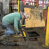 Terry Farrell fixes a hole in the floor at Dotson Iron Castings on Friday. The foundry is making repairs after part of it was damaged by a fire. Photo by Jackson Forderer