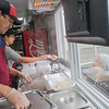 "Stacy Berkner (right) gives money to Deisy De Leon as Adam De Leon prepares Berkner's Mexican food in the On Every Corner food truck on Friday. It was the first day the De Leon's opened their food truck for business. ""Our plan is to go through the winter and test it out,"" said Deisy. Photo by Jackson Forderer"