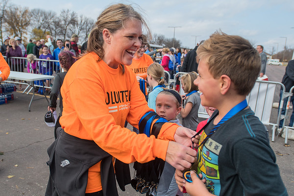 Cara Pipes (left) gives a medal to a participant at the finish line of the Kids K race on Saturday. Photo by Jackson Forderer