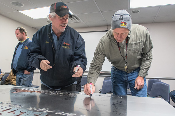 Jeff Sollinger (left) talks with Mark Maas as they sign a metal plaque donated by Jones Metal during an employee celebration at Dotson Iron Castings on Friday. Photo by Jackson Forderer