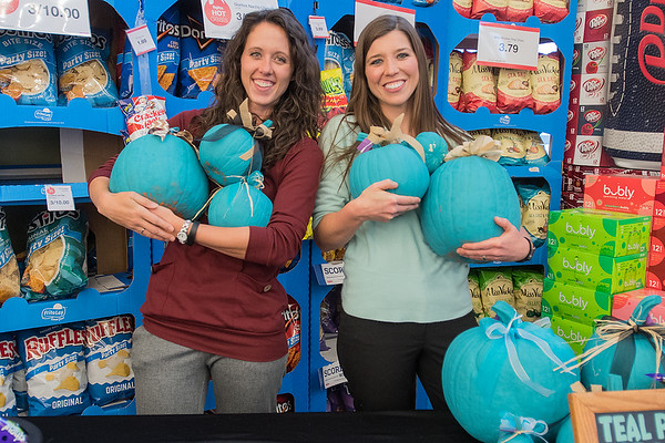 April Graff (left), a registered dietitian and Ashley Nuetzman, a nutrition dietitian assistant, hold teal pumpkins behind a display set up to promote the Teal Pumpkin Project at Hy Vee. Photo by Jackson Forderer